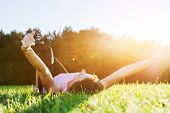 picture of harmony  - Young beautiful woman lying and stretching on the grass at spring summer sunset - JPG