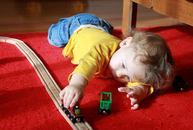 stock photo of track home  - Child toddler boy playing at home with trains and tracks - JPG
