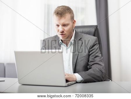 Businessman Looking At His Laptop In Disbelief