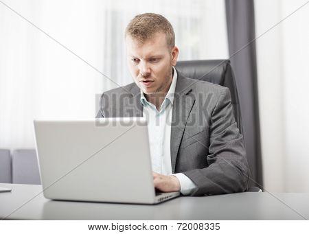 Businessman Looking At His Laptop In Disbelief