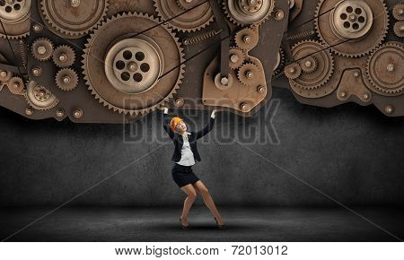 Young woman engineer holding mechanism of cogwheels above head
