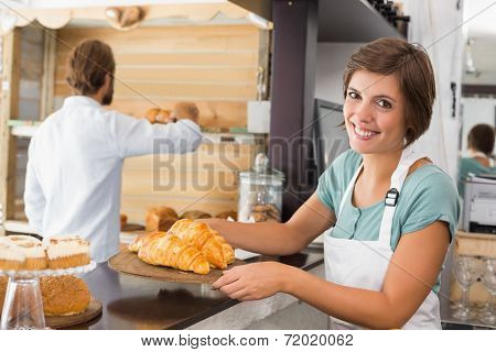Pretty waitress holding tray of croissants at the coffee shop