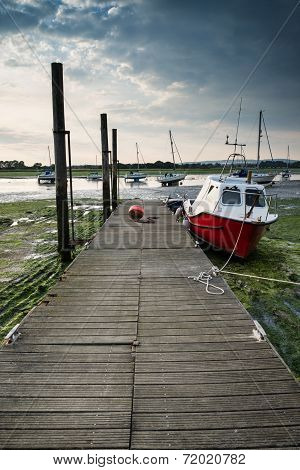Landscape Image Of Boats Mored To Jetty In Harbor During Summer Evening