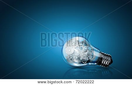 Conceptual image of light bulb with cogwheels inside