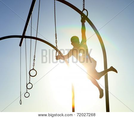 Athletic Man Using Rings at the Beach With Intentional Lensflare Creating a Silhouette