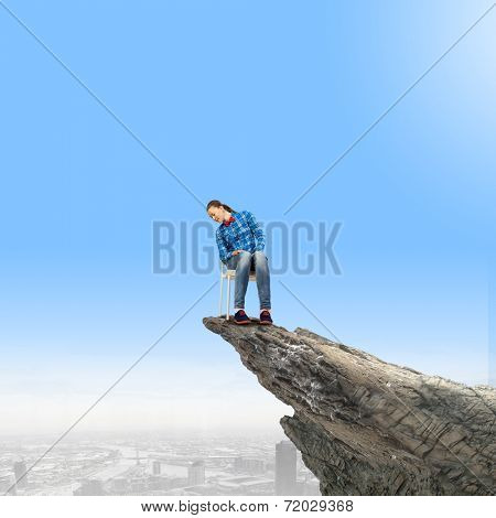 Young woman in shirt sitting in chair on rock top