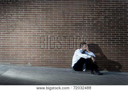 Businessman Who Lost Job Lost In Depression Sitting On City Street Corner