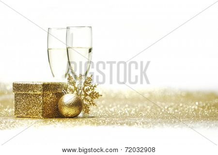 Champagne glasses and christmas decor on glitters with white copy space