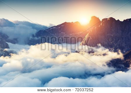 Great view of the foggy Val di Fassa valley with passo Sella. National Park. Dolomites, South Tyrol. Location Canazei, Campitello, Mazzin. Italy, Europe. Dramatic scene. Beauty world.