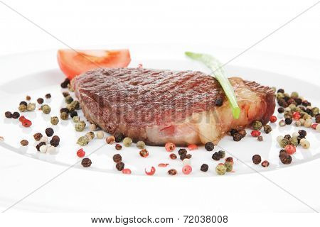 meat entree : grilled beef steak served with red tomato allspice pepper green chives on plate isolated over white background