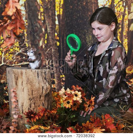 An attractive elementary girl viewing  a chipmunk through her magnifying glass.  They're in a woods surrounded by autumn colors.