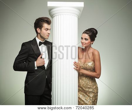 fashion elegant couple looking at each other near column in studio