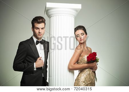 elegant couple posing near column, man in tuxedo and woman in evening gown with eyes closed