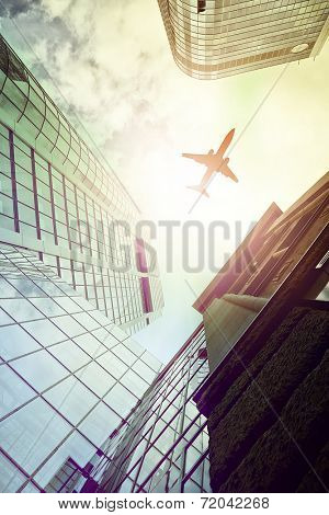 plane flying over highrise office buildings seen from below, Frankfurt am Main, Germany