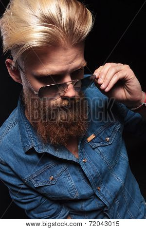 Long beard man in blue shirt looking down and fixing his sunglasses. On black background.