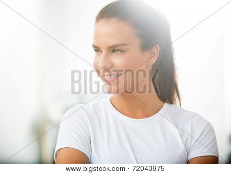 Thoughtful fit woman smiling while looking away at healthclub