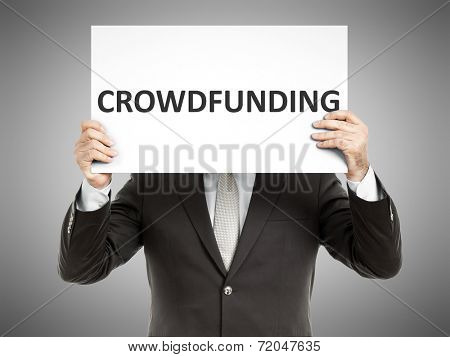 A business man holding a paper in front of his face with the text crowdfunding