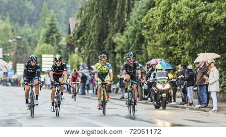 Four Cyclists Riding In The Rain
