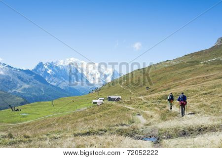 COL DE BALME, FRANCE - SEPTEMBER 01: Backpackers approraching chalet with Mont Blanc in the background. The area is a stage of the popular Mont Blanc tour. September 01, 2014 in Col de Balme.