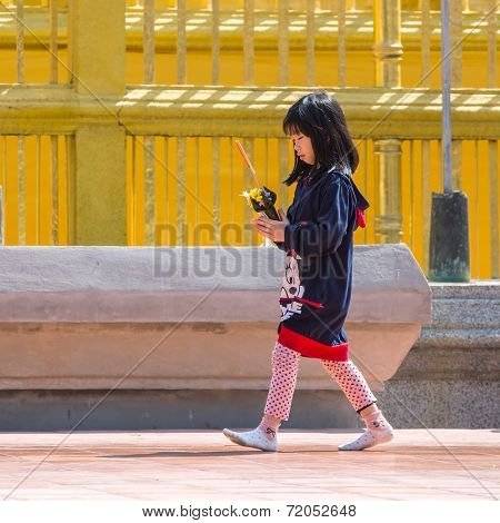 CHIANG MAI, THAILAND - JANUARY 25, 2014 :Unknown thai girl, pray before a Buddhist temple. The vast majority of people in Thailand are Buddhists.