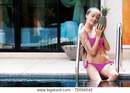 beautiful slim young  woman by the swimming pool with a pineapple
