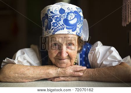 Old woman in traditional folk costume in  his house, close-up portrait.