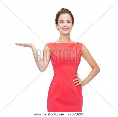 advertising and happy people concept - smiling woman in red dress holding something imaginary on palm of her hand
