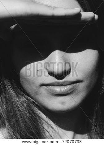 Close up head portrait of an attractive young woman shielding her eyes from the bright summer sun casting a dark mysterious shadow over her face