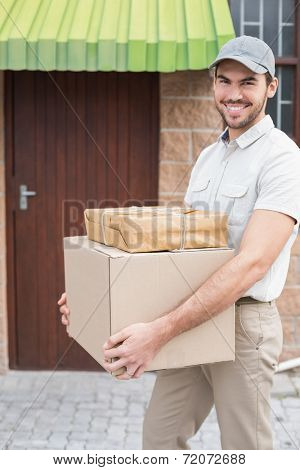 Delivery driver walking with parcels outside the warehouse