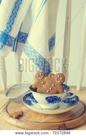 Homemade gingerbread men sitting in a vintage teacup