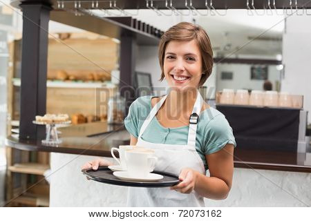 Waitress holding tray with cappuccinos at the coffee shop