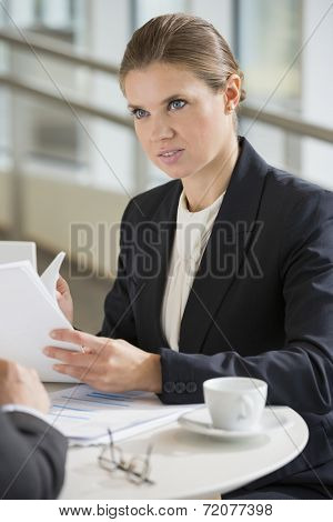 Businesswoman discussing with colleague during coffee break
