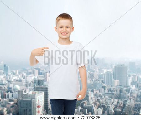 advertising, people and childhood concept - smiling little boy in white blank t-shirt pointing finger at himself over city background