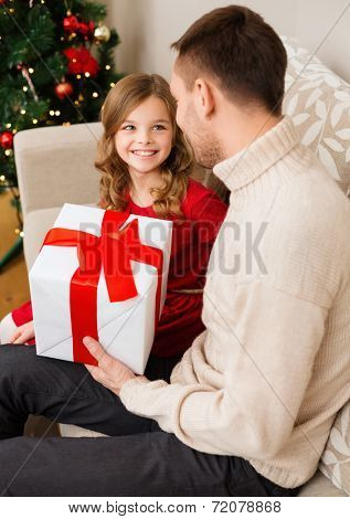 family, christmas, x-mas, happiness and people concept - smiling father and daughter holding gift box and looking at each other
