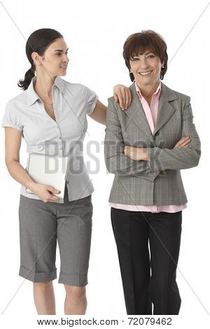 Young woman resting arm on mother's shoulder, holding tablet computer, both smiling.