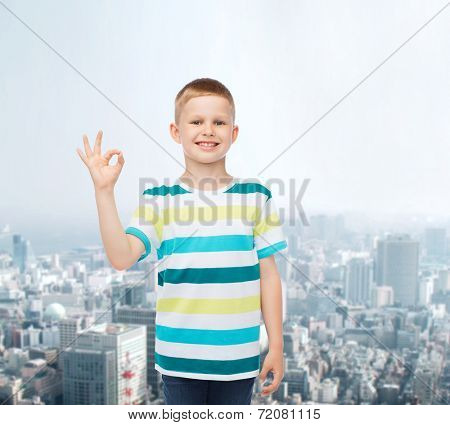 childhood, gesture and people concept - smiling little boy in casual clothes making ok gesture over city background