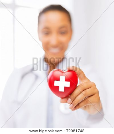 healthcare and medicine concept - female african american doctor holding heart with red cross symbol