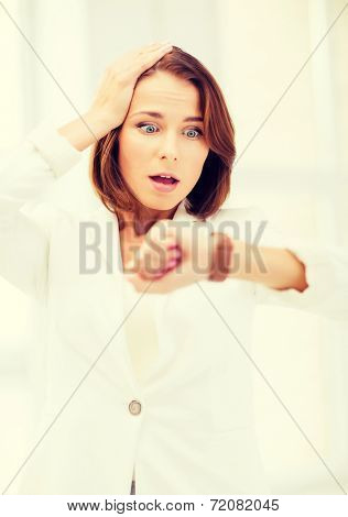 business and time management concept - stressed businesswoman looking at clock