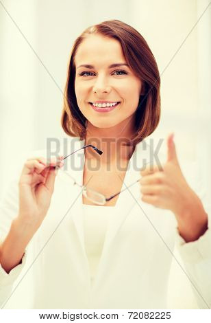 business and vision correction concept - businesswoman with eyeglasses showing thumbs up in office