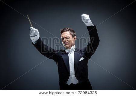 Emotional conductor in a tuxedo in studio