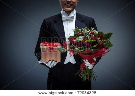 Young man in a tuxedo with a bouquet and gifts