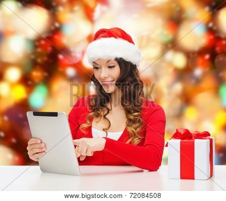 christmas, holidays, technology and people concept - smiling woman in santa helper hat with gift box and tablet pc computer over red lights background