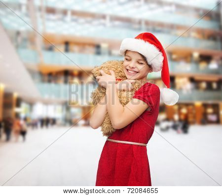 holidays, presents, christmas, childhood and people concept - smiling girl in santa helper hat with teddy bear over shopping center background