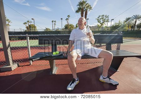 Happy senior male tennis player with water bottle sitting on bench at court