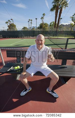 Portrait of happy senior male tennis player with water bottle relaxing on court