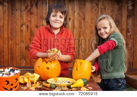 Kids carving their pumpkin jack-o-lanterns - removing the seeds