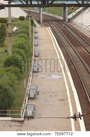 A view from above of an empty platform with benches at the railway station after rain in Novosibirsk