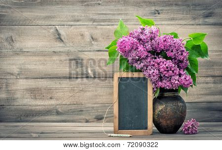 Lilac Flowers With Blackboard On Wooden Background