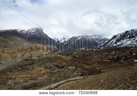 Small Lost Tibetan Village high in Himalayas Mountains with fields and mountain range on the backgro