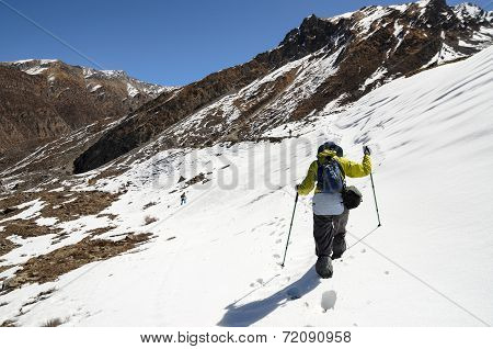 A Lonely Trekker Hiking Through Snow High In Mountains On A Bright Sunny Day